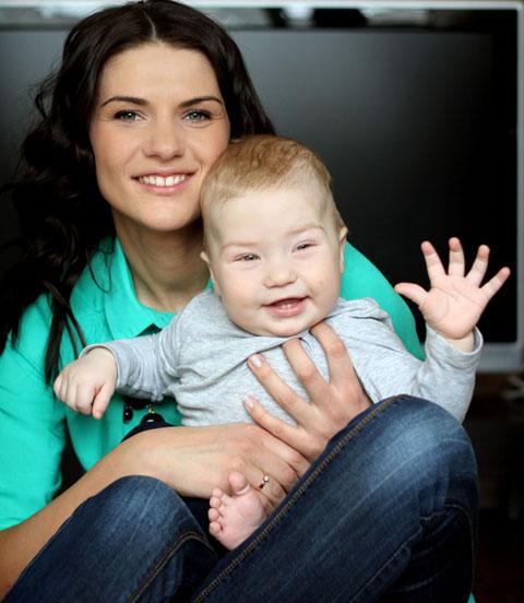 Au-pair mit freundlich winkendem Kleinkind auf dem Schoß